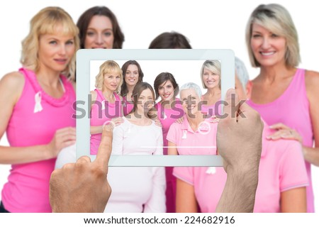Composite image of hand holding tablet pc showing photograph of breast cancer activists