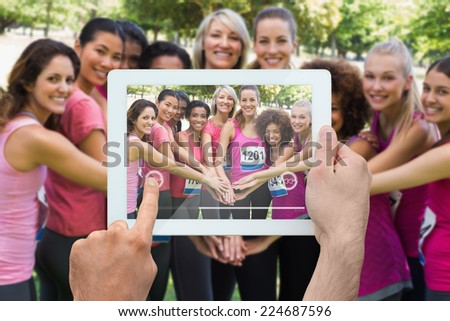 Composite image of hand holding tablet pc showing photograph of breast cancer activists - stock photo