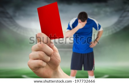 Composite image of hand holding up red card to player against football pitch in large stadium - stock photo