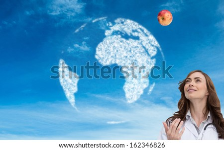 Composite image of happy brunette doctor throwing apple - stock photo