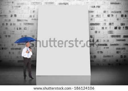 Composite image of happy businessman holding umbrella against white card - stock photo