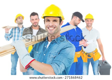 Composite image of happy carpenter carrying wooden planks - stock photo