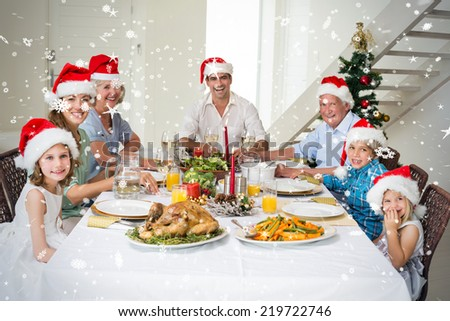 Composite image of Happy family in Santa hats having Christmas meal against snow falling - stock photo