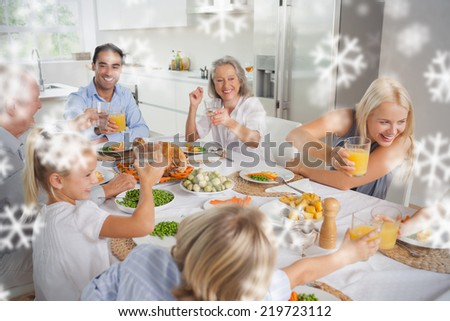 Composite image of Happy family raising their glasses together against snowflakes