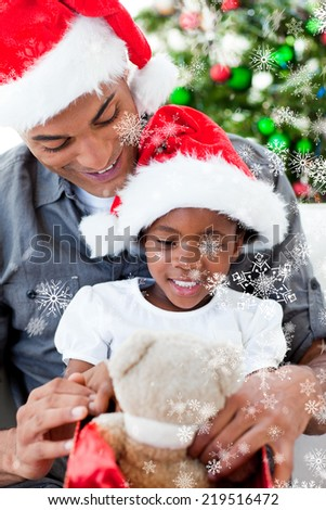 Composite image of Happy father and daughter playing with Christmas gifts with snow falling - stock photo