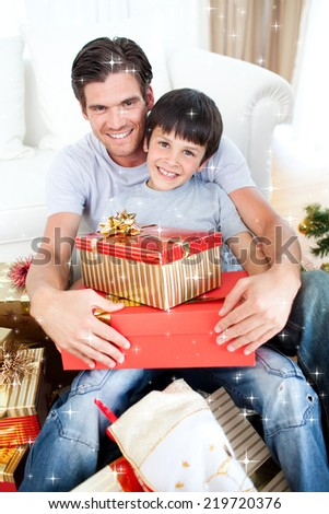 Composite image of Happy father and son holding Christmas gifts with twinkling stars