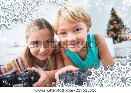 Composite image of happy siblings playing video games on floor against snow - stock photo