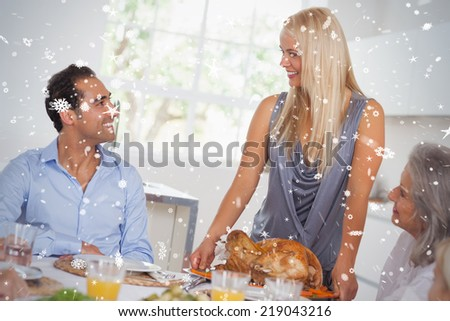 Composite image of Happy wife bringing turkey to the table against snow falling - stock photo