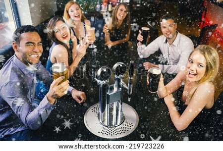 Composite image of Laughing friends raising their glasses up against snow - stock photo