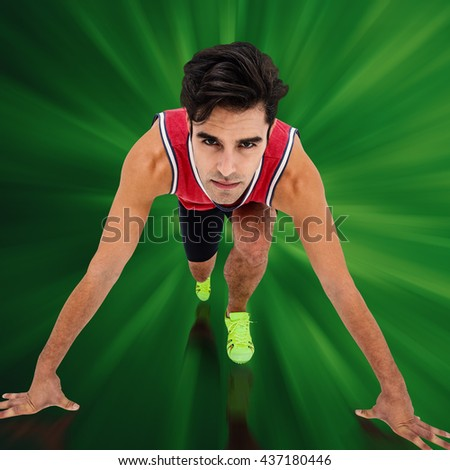 Composite image of male athlete in ready to run position against green background