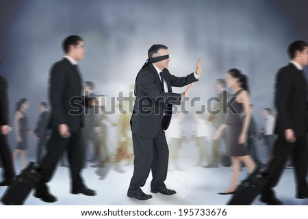 Composite image of mature businessman in a blindfold walking through crowd
