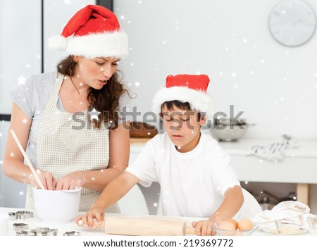 Composite image of Mother and son preparing Christmas biscuits together with snow - stock photo