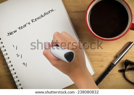Composite image of new years resolutions against overhead of notepad and pen and coffee - stock photo