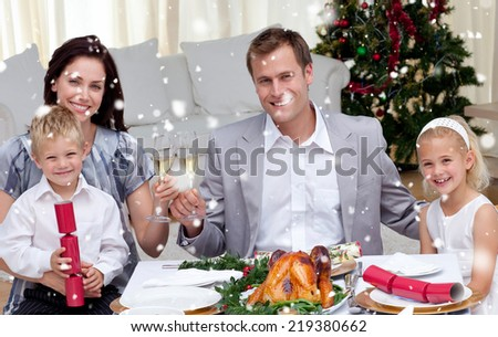 Composite image of Parents toasting with wine in Christmas dinner against snow falling - stock photo