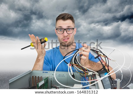 Composite image of portrait of confused young it professional with screw driver and cables in front of open cpu - stock photo