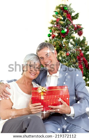 Composite image of Senior couple holding a Christmas present with snow falling