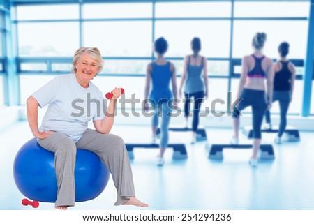 Composite image of senior woman sitting on exercise ball - stock photo