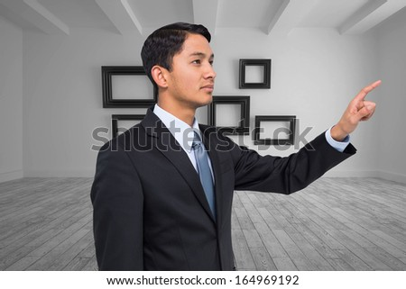 Composite image of serious asian businessman pointing