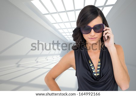 Composite image of serious elegant brunette wearing sunglasses on the phone - stock photo