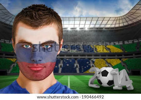 Composite image of serious young russia fan with face paint against large football stadium - stock photo