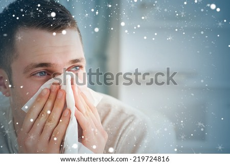 Composite image of sick man blowing his nose against snow - stock photo