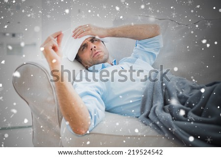 Composite image of sick man lying on sofa checking his temperature under a blanket against snow falling - stock photo