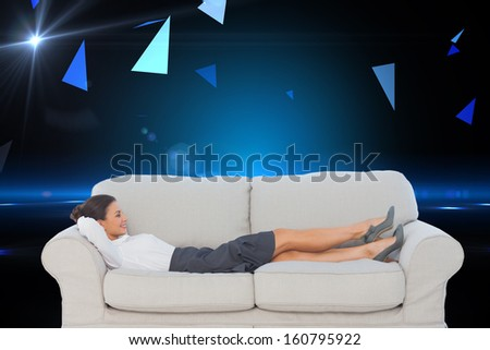 Composite image of smiling business woman lying down on the couch in the office