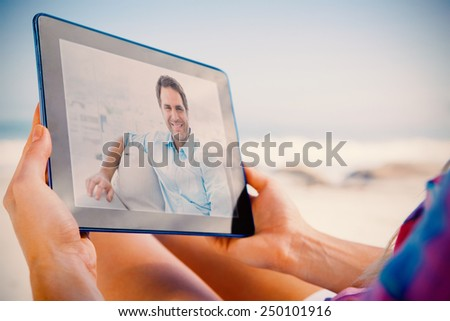 Composite image of smiling handsome man sitting on the couch looking at camera - stock photo