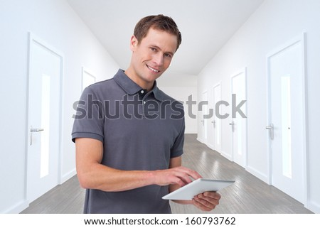 Composite image of smiling young man with tablet computer  - stock photo