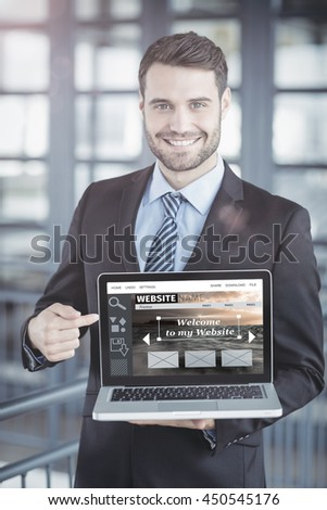 Composite image of website interface against happy businessman showing laptop - stock photo