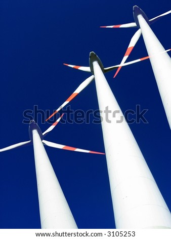 Composite image of wind generators against blue sky. - stock photo