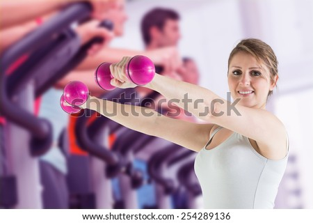 Composite image of woman holding weights - stock photo