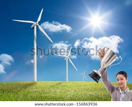 Composite image of young businesswoman showing a cup standing on windmill field - stock photo