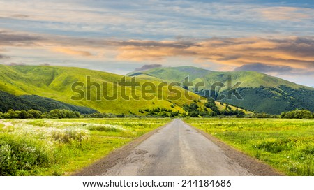 composite landscape with abandoned asphalt road rolls through meadows with flowers going to high  mountains in morning light - stock photo