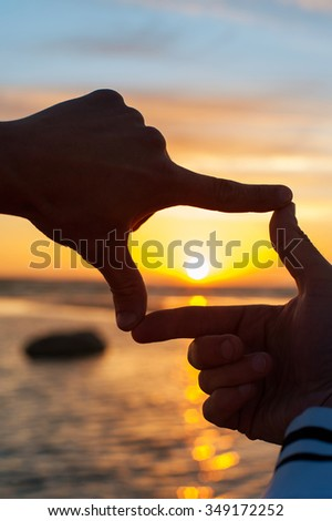 Composition finger frame- imitation of capturing rays of sunlight on sunset. Multicolored vertical outdoors image. - stock photo
