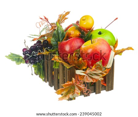 Composition from Artificial Fruits and Autumn Leaves in Wooden Box Isolated on White Background. Closeup. - stock photo