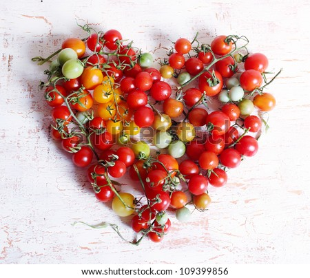 Composition in the form of heart from cherry tomatoes - stock photo