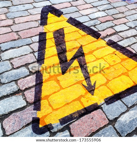 composition of a hazard warning sign on a cobblestone road