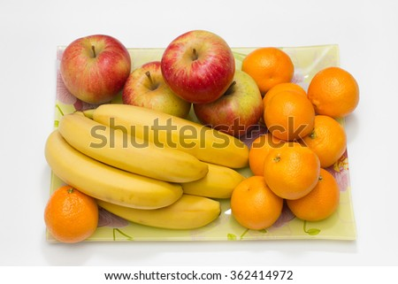 composition of apple banana and mandarin fruits on glass plate
