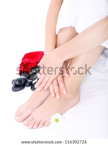 Composition of Beautiful woman legs, hands, spa stones with red pouch, and flower