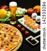 composition of beer sushi  and pizza on black background - stock photo