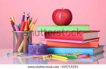 Composition of books, stationery and an apple on bright colorful background
