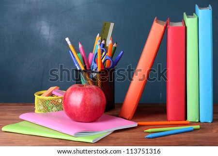 Composition of books, stationery and an apple on the teacher's desk in the background of the blackboard - stock photo