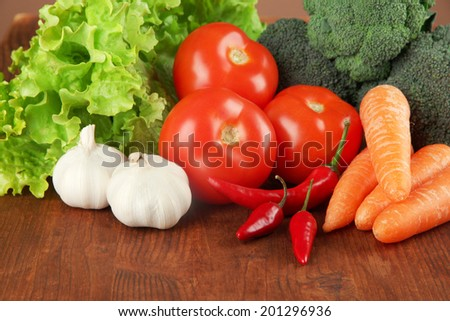 Composition of different vegetables on wooden background - stock photo