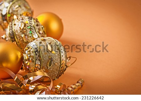 composition of golden christmas balls on light brown background - stock photo