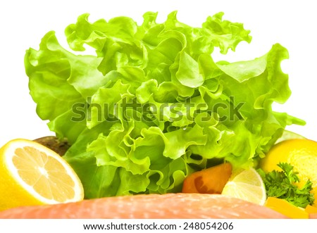 composition of green lettuce with yellow lemon, red tomato and red fish - stock photo