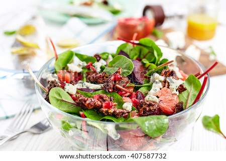 Composition of healthy dinner with beet and baby spinach salad , roasted seabass fish, feta cheese, pomergrat and citrus vinaigrette dressing. White wood background - stock photo