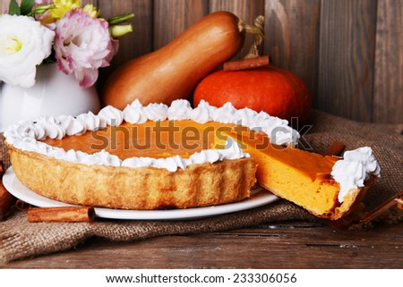 Composition of homemade pumpkin pie on plate and fresh pumpkins on wooden background - stock photo