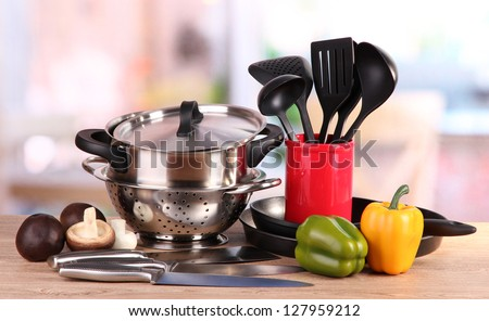 composition of kitchen tools and vegetables on table in kitchen - stock photo