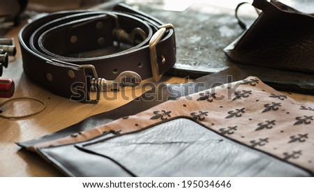 Composition of leather pieces of the leather bag on working desk with a low depth of field - stock photo